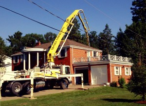 Photo of an APEX Concrete Pump arm extending over a two story home